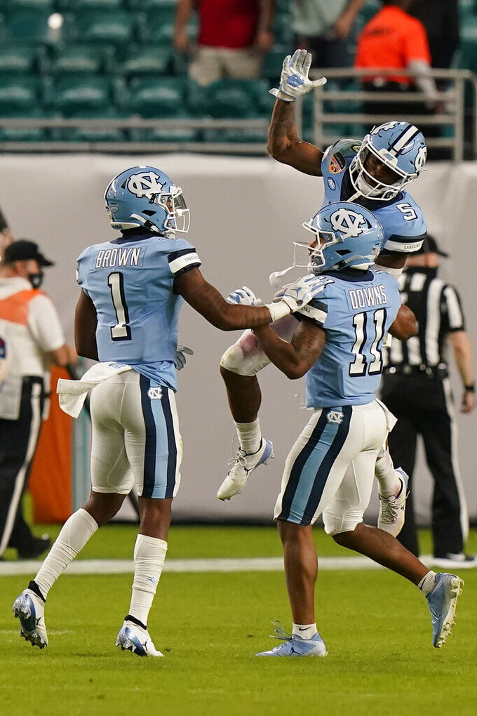 North Carolina wide receivers Dazz Newsome (5) and Khafre Brown (1) congratulate wide receiver Josh Downs (11) after Downs scored a touchdown during the second half of the Orange Bowl NCAA college football game against Texas A&M, Saturday, Jan. 2, 2021, in Miami Gardens, Fla. (AP Photo/Lynne Sladky)