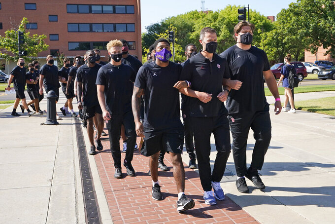 Defensive back Chanse Sylvie, left, head coach Lincoln Riley, center, and offensive lineman Creed Humphrey, right, lead the Oklahoma football team on a march to the Unity Garden to protest racial injustice in Norman, Okla., Friday, Aug. 28, 2020. (AP Photo/Sue Ogrocki)