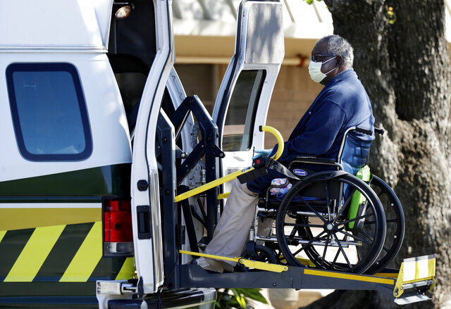 A resident is removed from the Southeast Nursing and Rehabilitation Center in San Antonio, Wednesday, April 1, 2020. Multiple people have tested positive for COVID-19 at the facility. (AP Photo/Eric Gay)