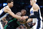 Boston Celtics' Terry Rozier (12) struggles to control the ball against Orlando Magic's Michael Carter-Williams, left, and Aaron Gordon during the first half of an NBA basketball game in Boston, Sunday, April 7, 2019. (AP Photo/Michael Dwyer)