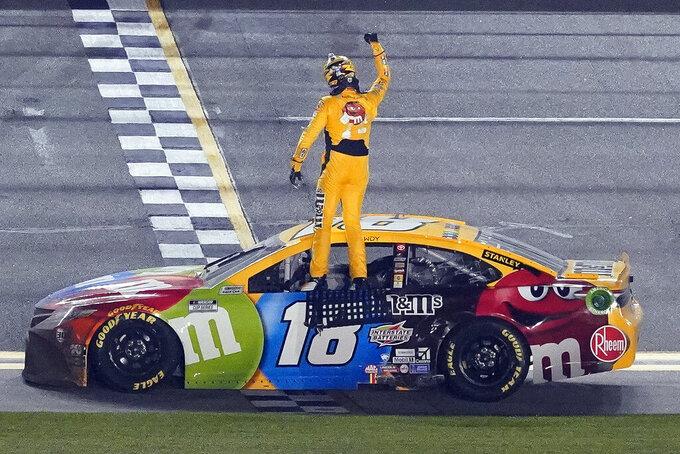 Kyle Busch celebrates on the top of his car after winning the NASCAR Clash auto race at Daytona International Speedway, Tuesday, Feb. 9, 2021, in Daytona Beach, Fla. (AP Photo/John Raoux)
