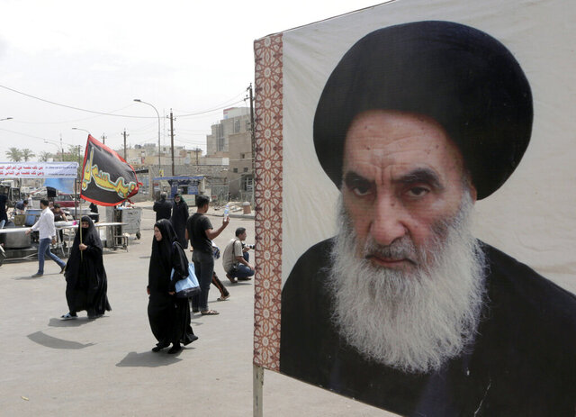 FILE - In this May 22, 2014 file photo, shiite pilgrims pass a poster of Shiite spiritual leader Grand Ayatollah Ali al-Sistani, as they head to the shrine of Imam Moussa al-Kadhim in Baghdad, Iraq. Iraq's most revered Shiite cleric whose opinion is often sought during troubled times will undergo surgery for a fractured bone, according to two officials and a statement from his office on Thursday. (AP Photo/Khalid Mohammed, File)