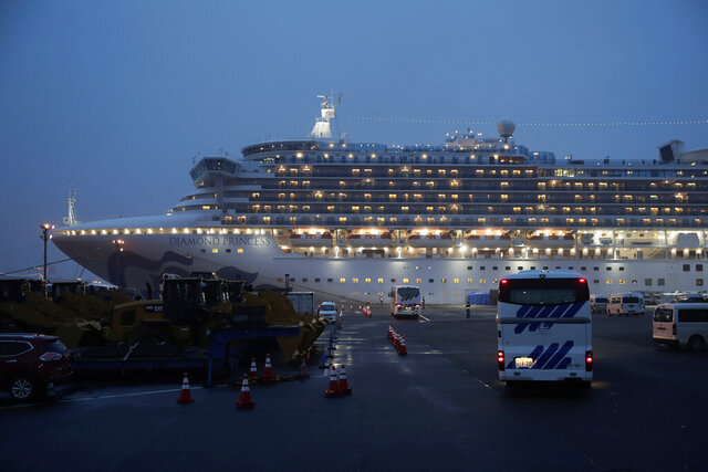 Buses arrive at a port as the Japan Self-Defense Forces prepare to move American passengers from the quarantined Diamond Princess cruise ship Sunday, Feb. 16, 2020, at Yokohama Port, near Tokyo. The U.S. says Americans aboard a quarantined ship will be flown back home on a chartered flight Sunday, but that they will face another two-week quarantine. (AP Photo/Jae C. Hong)