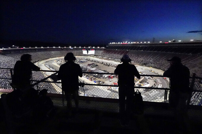 Spotters watch from a rooftop during a NASCAR Xfinity Series auto race at Bristol Motor Speedway Friday, Sept. 17, 2021, in Bristol, Tenn. (AP Photo/Mark Humphrey)