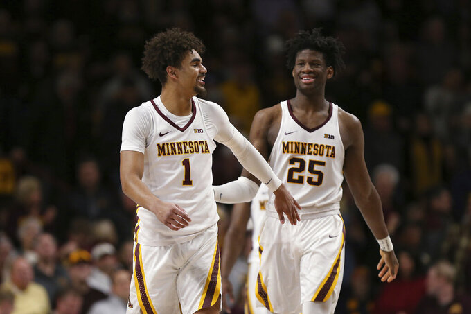 Minnesota's Tre' Williams (1) smiles with teammate Minnesota's Daniel Oturu (25) during an NCAA college basketball game against Northwestern, Sunday, Jan. 5, 2020, in Minneapolis. Minnesota won 77-68. (AP Photo/Stacy Bengs)