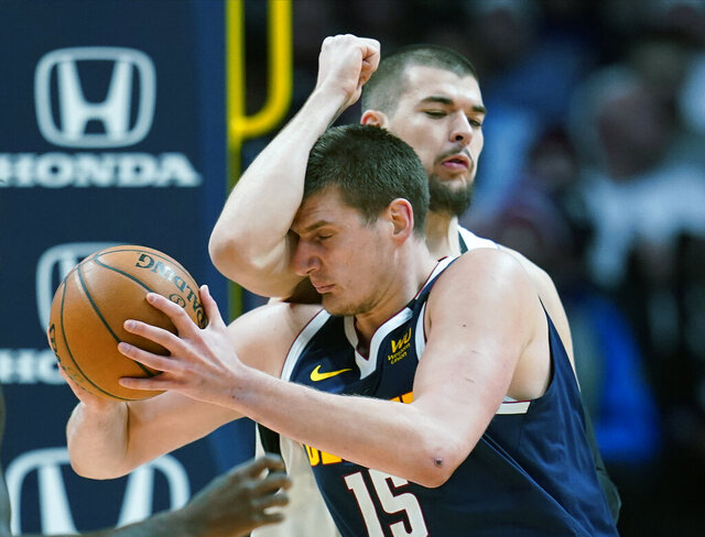 Denver Nuggets center Nikola Jokic (15) drives his head into Los Angeles Clippers center Ivica Zubac (40) during the second quarter of an NBA basketball game, Sunday, Jan. 12, 2020, in Denver. (AP Photo/Jack Dempsey)