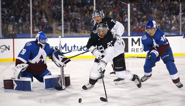 Los Angeles Kings defenseman Alec Martinez, center, looks to redirect the puck, between Colorado Avalanche goaltender Pavel Francouz, left, and defenseman Samuel Girard during the third period of an NHL hockey game Saturday, Feb. 15, 2020, at Air Force Academy, Colo. The Kings won 3-1. (AP Photo/David Zalubows