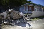 A big rock sits amid the rubble of the low wall it destroyed when it rolled down from a nearby cliff during a magnitude 5.9 earthquake in Guanica, Puerto Rico, Saturday, Jan. 11, 2020. The morning quake caused further damage along the island's southern coast, where previous recent quakes have toppled homes and schools. (AP Photo/Carlos Giusti)