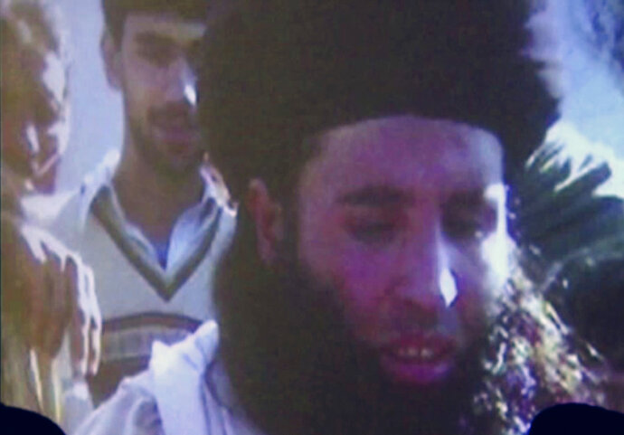 FILE - In this file image made from video broadcast on Thursday, Nov. 7, 2013, undated footage of Mullah Fazlullah is shown on a projector in Pakistan. An Afghan defense ministry official says Friday, June 15, 2018 a US drone strike in northeastern Kunar province killed Pakistan Taliban chief Mullah Fazlullah. Pakistan has been hunting Fazlullah for several years and has repeatedly said he was plotting attacks on Pakistan from safe havens in Afghanistan.  (AP Photo via AP Video, File)