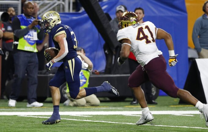 Georgia Tech running back Nathan Cottrell (31) pulls away from Minnesota linebacker Thomas Barber (41) for a 20-yard touchdown run during the second half of the Quick Lane Bowl NCAA college football game, Wednesday, Dec. 26, 2018, in Detroit. (AP Photo/Carlos Osorio)