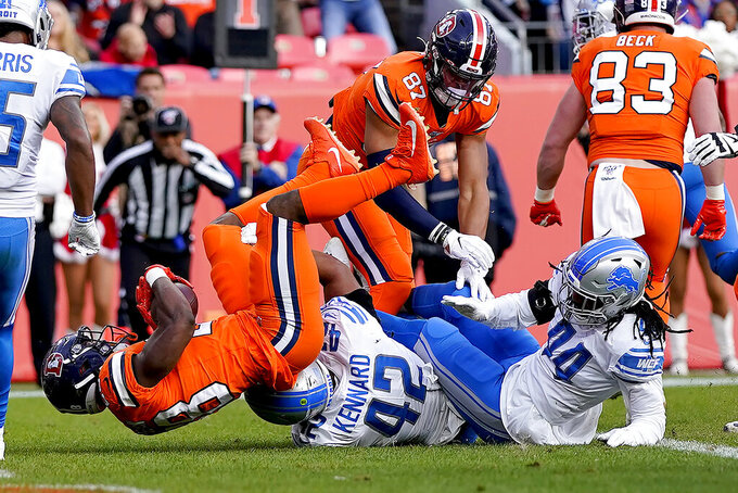 Denver Broncos running back Royce Freeman scores a touchdown as Detroit Lions outside linebacker Devon Kennard (42) defends during the first half of an NFL football game, Sunday, Dec. 22, 2019, in Denver. (AP Photo/Jack Dempsey)