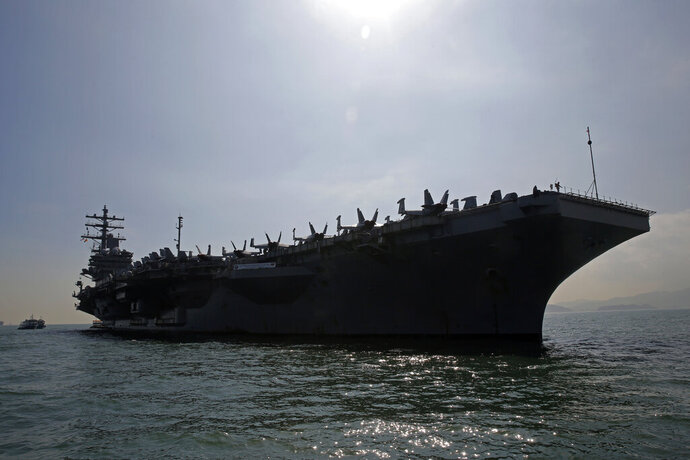 """FILE - In this Nov. 21, 2018, file photo, the U.S. Navy's USS Ronald Reagan aircraft carrier is anchored in Hong Kong. The U.S. 7th Fleet said Sunday the ships and aircraft from the Ronald Reagan Carrier Strike Group and the Boxer Amphibious Ready Group staged joint, """"high-end warfighting exercises"""" in the South China Sea. (AP Photo/Kin Cheung, File)"""