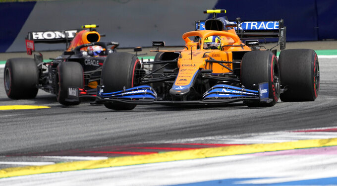 Mclaren driver Lando Norris of Britain leads ahead of Red Bull driver Sergio Perez of Mexiconduring the Styrian Formula One Grand Prix at the Red Bull Ring racetrack in Spielberg, Austria, Sunday, June 27, 2021. (AP Photo/Darko Vojinovic)