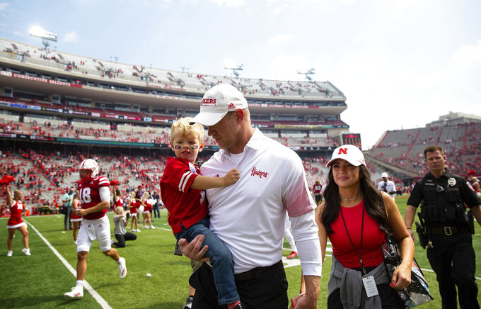 Nebraska head coach Scott Frost carries his son, RJ, 3, while exiting the field hand-in-hand with his wife, Ashley, following the Huskers' 52-7 victory over Fordham in an NCAA college football game Saturday, Sept. 4, 2021, at Memorial Stadium in Lincoln, Neb. (AP Photo/Rebecca S. Gratz)