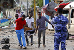 Somalis carry away an injured civilian who was wounded in a bomb blast near the Sahafi hotel in the capital Mogadishu, Somalia Friday, Nov. 9, 2018. Three car bombs by Islamic extremists exploded outside the hotel, which is located across the street from the police Criminal Investigations Department, killing at least 10 people according to police. (AP Photo/Farah Abdi Warsameh)