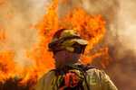 A firefighter watches the Apple Fire in Cherry Valley, Calif., Saturday, Aug. 1, 2020. A wildfire northwest of Palm Springs flared up Saturday afternoon, prompting authorities to issue new evacuation orders as firefighters fought the blaze in triple-degree heat.(AP Photo/Ringo H.W. Chiu)