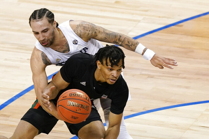 Georgia Tech guard Jose Alvarado (10) reaches around to get the ball from Miami guard Isaiah Wong (2) during the second half of an NCAA college basketball game in the quarterfinal round of the Atlantic Coast Conference tournament in Greensboro, N.C., Thursday, March 11, 2021. (AP Photo/Gerry Broome)