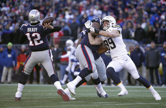 New England Patriots quarterback Tom Brady (12) passes while tackle Marcus Cannon blocks Los Angeles Chargers defensive end Joey Bosa (99) during the first half of an NFL divisional playoff football game, Sunday, Jan. 13, 2019, in Foxborough, Mass. (AP Photo/Elise Amendola)
