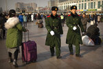 Chinese paramilitary police patrol outside of the Beijing Railway Station in Beijing, Friday, Jan. 17, 2020. As the Lunar New Year approached, Chinese travelers flocked to train stations and airports Friday to take part in a nationwide ritual: the world's biggest annual human migration. (AP Photo/Mark Schiefelbein)