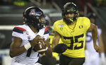 Arizona quarterback Khalil Tate, left, looks for a receiver as Oregon's Troy Dye closes in during the fourth quarter of an NCAA college football game Saturday, Nov. 16, 2019, in Eugene, Ore. (AP Photo/Chris Pietsch)