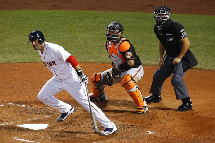 Boston Red Sox's J.D. Martinez, left, follows through on an RBI-double in front of Baltimore Orioles' Pedro Severino during the third inning of an opening day baseball game at Fenway Park, Friday, July 24, 2020, in Boston. (AP Photo/Michael Dwyer)