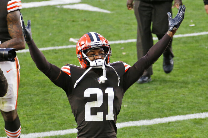 FILE - In this Sunday, Nov. 15, 2020 file photo, Cleveland Browns cornerback Denzel Ward celebrates after the Browns defeated the Houston Texans 10-7 after an NFL football game in Cleveland. The Browns are trying to shake free from COVID-19 to face the Steelers. Cleveland's issues with the virus intensified Thursday, Dec. 31, 2020 as top cornerback Denzel Ward and linebacker Malcolm Smith were placed on the COVID-19 reserve list and the team was forced to close its facility before canceling practice with the biggest game in decades coming fast.(AP Photo/Ron Schwane, File)