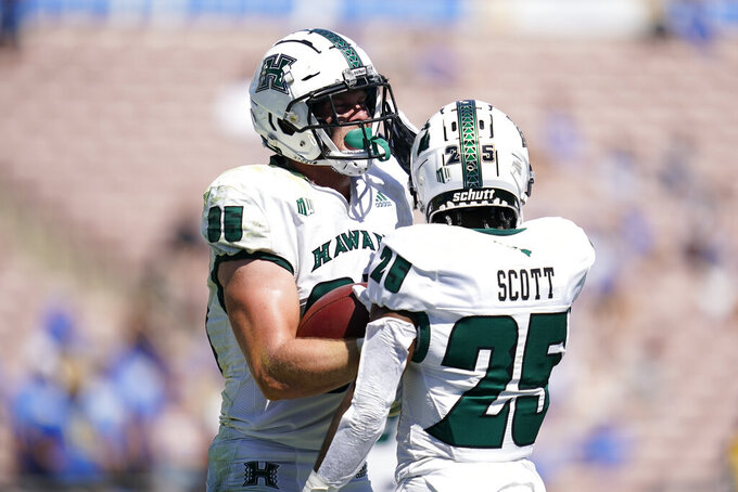 Hawaii tight end Caleb Phillips (85) celebrates with running back Dior Scott (25) after scoring a touchdown during the second half of an NCAA college football game against UCLA Saturday, Aug. 28, 2021, in Pasadena, Calif. (AP Photo/Ashley Landis)