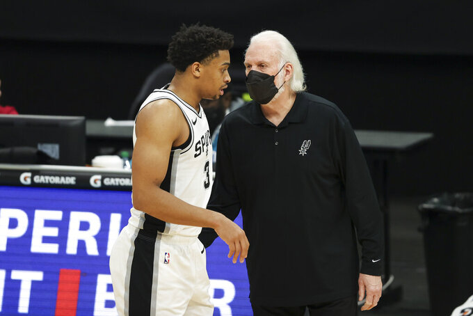 San Antonio Spurs coach Gregg Popovich, right, talks to San Antonio Spurs forward Keldon Johnson during the second half of an NBA basketball game against the Charlotte Hornets in Charlotte, N.C., Sunday, Feb. 14, 2021. (AP Photo/Nell Redmond)