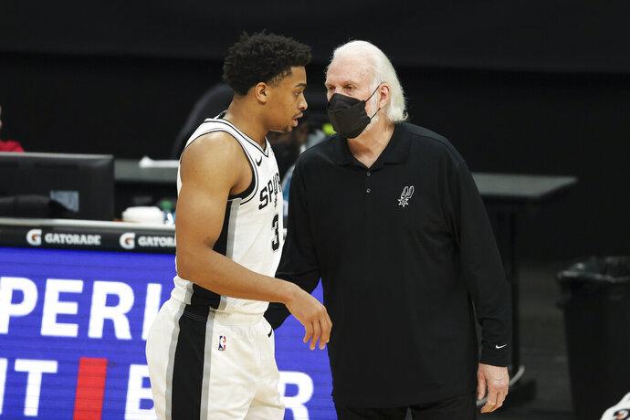 San Antonio Spurs coach Gregg Popovich, right, talks to San Antonio Spurs forward Keldon Johnson during the second half of an NBA basketball game against the Charlotte Hornets in Charlotte, N.C., Sunday, Feb. 14, 2021. (AP Photo/Nell Redmond)