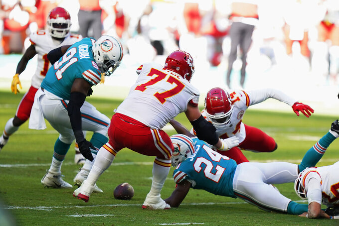 Miami Dolphins cornerback Byron Jones (24) fumbles the ball after intercepting a pass, while defensive end Emmanuel Ogbah (91) is ready to pick it up, during the first half of an NFL football game against the Kansas City Chiefs, Sunday, Dec. 13, 2020, in Miami Gardens, Fla. (AP Photo/Wilfredo Lee)