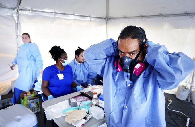 Mark Thompson, of Clearwater, dons a variety of PPE, including a respirator mask, before administering a COVID-19 viral test on Wednesday, May 6, 2020, at Community Health Centers of Pinellas, in Clearwater where Pinellas County began COVID-19 testing on Monday.(Douglas R. Clifford/Tampa Bay Times via AP)
