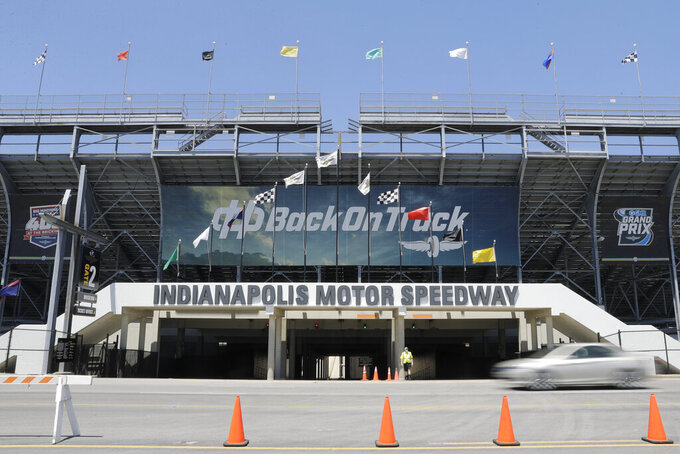 A car drives past an entrance to the Indianapolis Motor Speedway in Indianapolis, Thursday, July 2, 2020. Roger Penske has spent the six months since he bought Indianapolis Motor Speedway transforming the facility. He's spent millions on capital improvements to the 111-year-old national landmark and finally gets to showcase some of the upgrades this weekend as NASCAR and IndyCar share the venue in a historic doubleheader. (AP Photo/Darron Cummings)