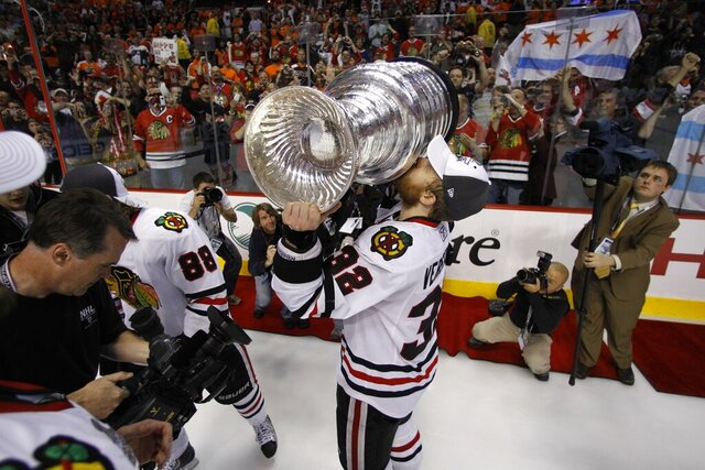 FILE - In this June 9, 2010, file photo, Chicago Blackhawks' Kris Versteeg celebrates with the Stanley Cup after winning Game 6 of the NHL Stanley Cup hockey finals against the Philadelphia Flyers in Philadelphia.  Two-time Stanley Cup-winning forward Kris Versteeg is retiring after 11 NHL seasons. The 33-year-old announced his decision through the NHL Players' Association on Tuesday, April 14, 2020, and after ending this season playing with his brother, Mitch, with Slovakia's HK Nitra.  (AP Photo/Matt Slocum)