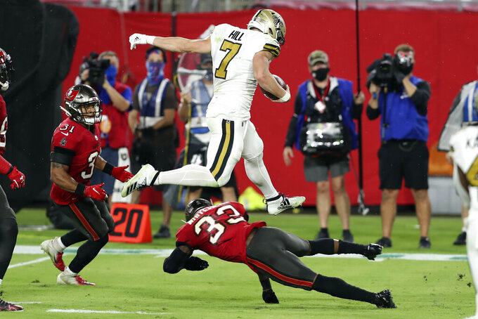 New Orleans Saints quarterback Taysom Hill (7) leaps over Tampa Bay Buccaneers free safety Jordan Whitehead (33) on a run during the first half of an NFL football game Sunday, Nov. 8, 2020, in Tampa, Fla. (AP Photo/Mark LoMoglio)