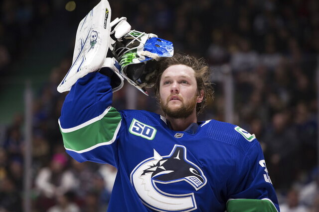 """FILE - In this Jan. 27, 2020 file photo, Vancouver Canucks goalie Thatcher Demko takes off his mask during a stoppage in play against the St. Louis Blues during the first period of an NHL hockey game in Vancouver, British Columbia. NHL players are debating the merits of quarantining away from family members as part of a potential resumption of the season.  Young and single, Demko said quarantining to play hockey wouldn't be a problem for him. """"I don't have too many roots,"""" the 24-year-old said. """"I've been living pretty much out of my car for the most part for the last six, seven years just going from place to place."""" (Darryl Dyck/The Canadian Press via AP, File)"""