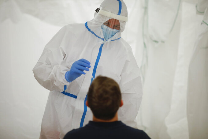 Medical staff of the German Red Cross, DRK, wears protective suit as he takes a coronavirus test at a newly set up test station at the main train station in Berlin, Germany, Monday, Aug. 17, 2020. Travellers arriving from countries considered 'at-risk' can be tested for the coronavirus free of charge at the station.(Photo/Markus Schreiber)