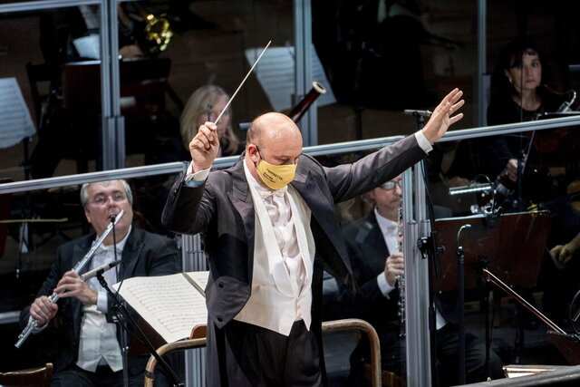 Musical director Riccardo Frizza, wearing a face mask to curb the spread of COVID-19, directs the orchestra during rehearsals for Gaetano Donizetti's opera, Marino Faliero, at the Donizetti theater in Bergamo, Italy, Thursday, Nov. 18, 2020. In a signal of rebirth, the Donizetti theater in the northern Italian city of Bergamo  devastated by coronavirus reopened this weekend after three years of renovations.   (Gianfranco Rota/Teatro Donizetti via AP)