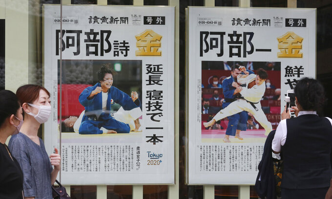 """FILE - In this July 26, 2021, file photo, people wearing face masks to protect against the spread of the coronavirus walk past extra papers reporting that Japanese judoka siblings won gold medal at Tokyo 2020 Olympics, in Tokyo. When the Tokyo Olympics began during a worsening pandemic, the majority of the host nation was in opposition, with Emperor Naruhito dropping the word """"celebrating"""" from his opening declaration of welcome. But once the Games got underway and local media switched to covering Japanese athletes' """"medal rush,"""" many were won over. (AP Photo/Koji Sasahara, File)"""