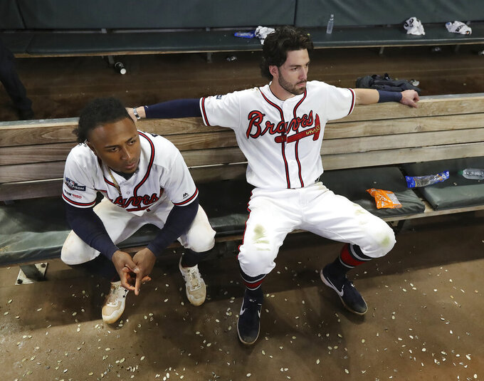 Atlanta Braves Ozzie Albies, left, and Dansby Swanson watch from the dugout during the ninth inning of the team's 13-1 loss to the St. Louis Cardinals during Game 5 of a baseball National League Division Series on Wednesday, Oct. 9, 2019, in Atlanta. The Cardinals advanced to the NL Championship Series. (Curtis Compton/Atlanta Journal-Constitution via AP)