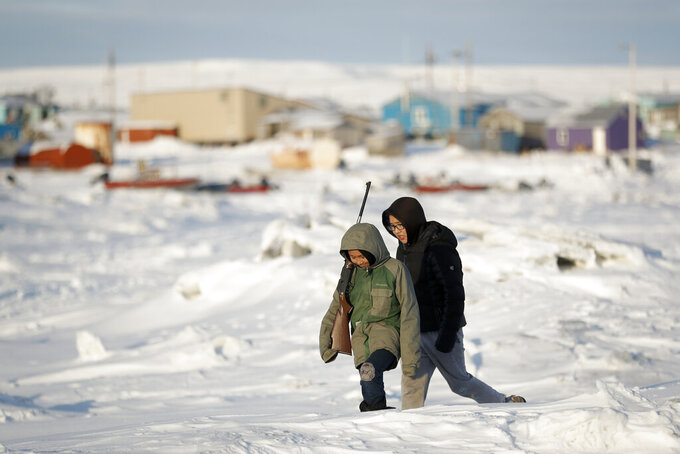 FILE - In this Jan. 18, 2020, file photo, George Chakuchin, left, and Mick Chakuchin walk on ice over the Bering Sea in Toksook Bay, Alaska, a mostly Yuip'ik village. Native American leaders are raising questions about how $8 billion in federal coronavirus relief tagged for tribes will be distributed, with some arguing that for-profit Alaska Native corporations shouldn't get a share of the funding. (AP Photo/Gregory Bull, File)