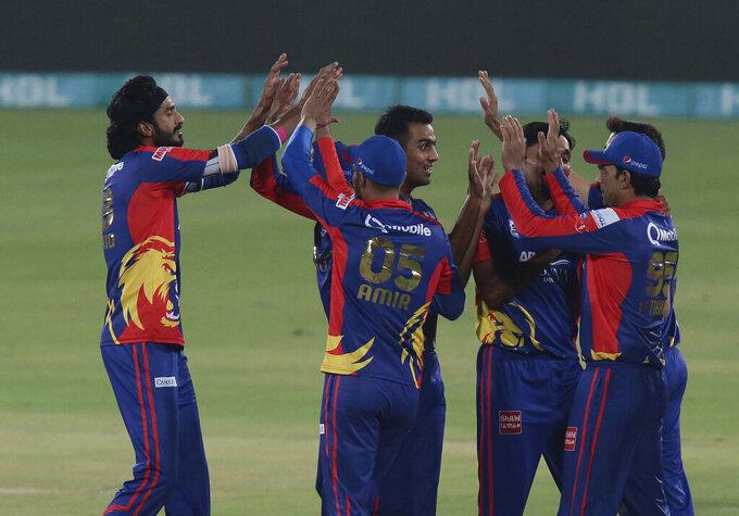 Karachi Kings pacer Umaid Asif, left, celebrates with teammates after taking the wicket of Qalandars batsman Tamim Iqbal during the final of Pakistan Super League T20 cricket match at National Stadium in Karachi, Pakistan, Tuesday, Nov. 17, 2020. (AP Photo/Fareed Khan)