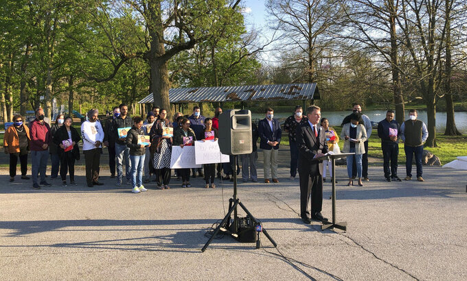 Indianapolis Mayor Joe Hogarth speaks at a vigil Saturday, April 17, 2021 at Krannert Park on Indianapolis' west side to memorialize the eight people killed in the mass shooting at a FedEx warehouse. Behind him, members of the Sikh community, whose loved ones were killed, hold signs demanding policymakers make gun law reforms in the wake of the shooting. (AP Photo/Casey Smith)