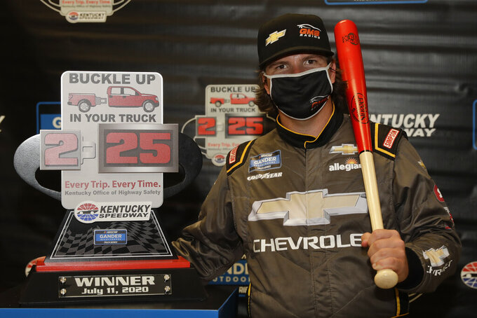 Sheldon Creed poses with the trophy after winning a weather shortened NASCAR Truck Series race Saturday, July 11, 2020, in Sparta, Ky. (AP Photo/Mark Humphrey)