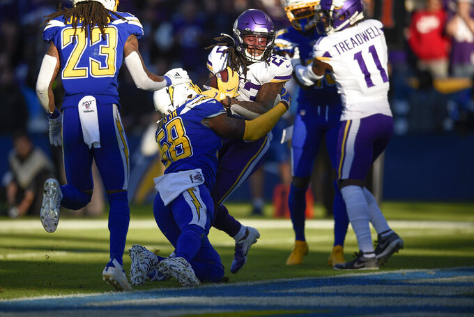 Minnesota Vikings running back Mike Boone, center, scores a touchdown as Los Angeles Chargers outside linebacker Thomas Davis defends during the second half of an NFL football game Sunday, Dec. 15, 2019, in Carson, Calif. (AP Photo/Kelvin Kuo)