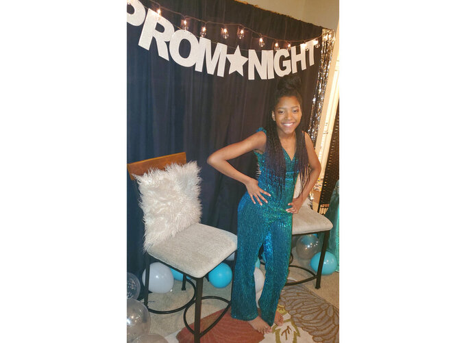 This photo shows Serenity Cadogan, 12, in Covington, Georgia, dressed for a virtual prom she hosted March 31 on National Prom Day for more than 600 young people around the world. With the Class of 2020 missing out on so many traditions due to the coronavirus pandemic, many have gone online to participate in virtual proms. (Tiffany Cadogan via AP)