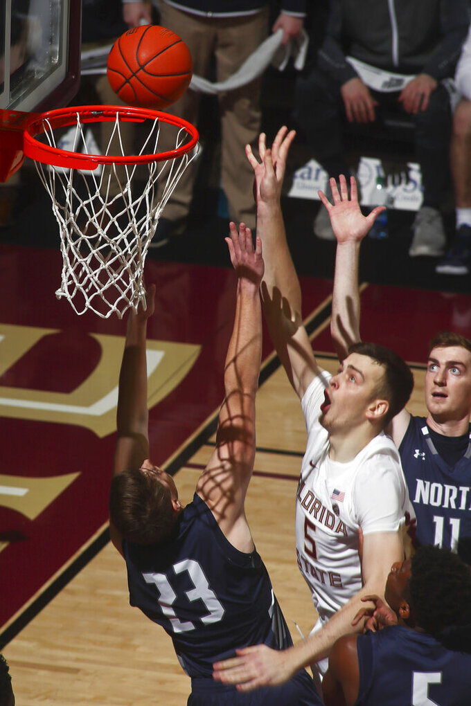 Florida State center Balsa Koprivica (5) makes a layup as he is fouled by North Florida forward Carter Hendricksen (23) in the first half of an NCAA college basketball game in Tallahassee, Fla., Tuesday, Dec. 17, 2019. (AP Photo/Phil Sears)