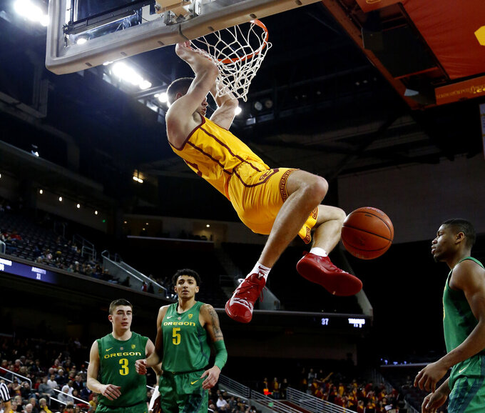 Southern California's Nick Rakocevic, second from right, dunks against Oregon during the second half of an NCAA college basketball game Thursday, Feb. 21, 2019, in Los Angeles. (AP Photo/Ringo H.W. Chiu)