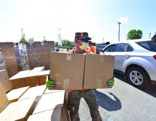 Vermont National Guard Sgt. Michael Menard grabs boxes of food and loads them onto people's vehicles at a Farmers to Families Food Box Distribution site at Brattleboro Union High School, in Brattleboro, Vt., on Wednesday, May 27, 2020. (Kristopher Radder/The Brattleboro Reformer via AP)