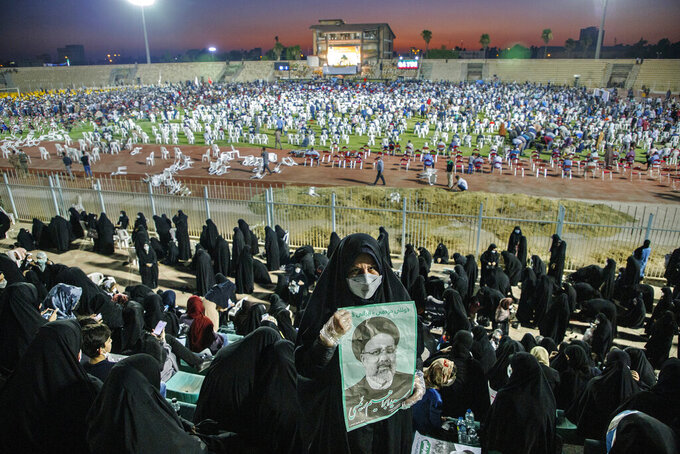 In this Wednesday, June 9, 2021, photo, a supporter of the presidential candidate Ebrahim Raisi, currently judiciary chief, hold posters of him during a campaign rally at the Takhti Stadium in Ahvaz, Iran. Around 5,000 of people have gathered in a football stadium in southeastern city of Ahvaz to support the Iranian hard-line presidential candidate, Iranian media reported. (Amin Nazari/ISNA via AP)