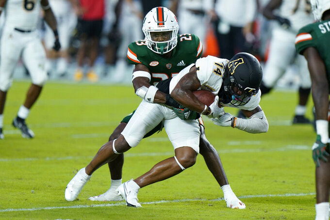 Appalachian State wide receiver Malik Williams (14) is taken down by Miami cornerback Te'Cory Couch (23) during the first half of an NCAA college football game, Saturday, Sept. 11, 2021, in Miami Gardens, Fla. (AP Photo/Wilfredo Lee)